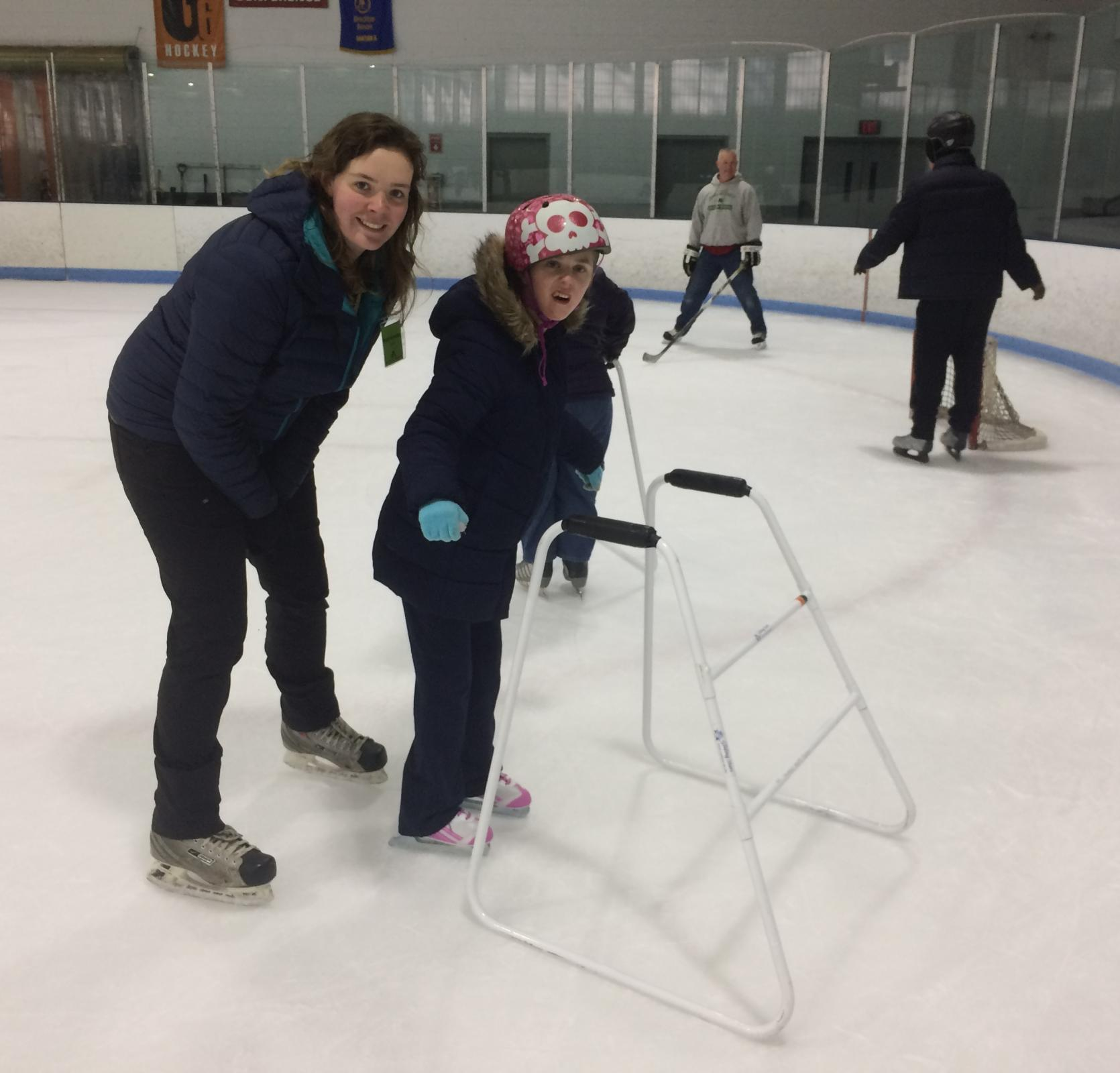 A young skater wearing a colorful helmet is standing in the foreground holding her arms out for balance. A skate walker is in front of her, and a staff member is standing behind her. They are both smiling at the camera. Behind them, two other skaters skate around a small hockey net.