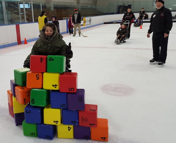 A woman wearing a thick faux fur hood is crashing through a tower of colorful blocks in her power wheelchair. Behind her, other skaters are being pushed in ice sleds by Durfee High School hockey players, or using skates and helmets.