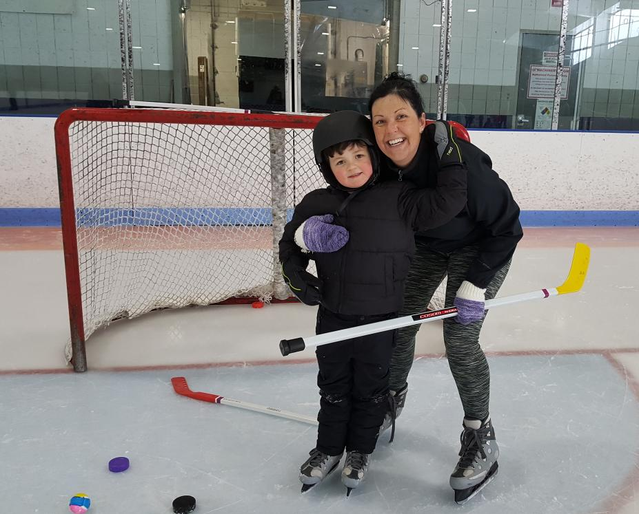 A woman and a child are wearing ice skates and standing in front of a hockey net. The woman is bending down and the two are hugging each other and smiling. There are colorful hockey sticks and pucks on the ice in front of them.
