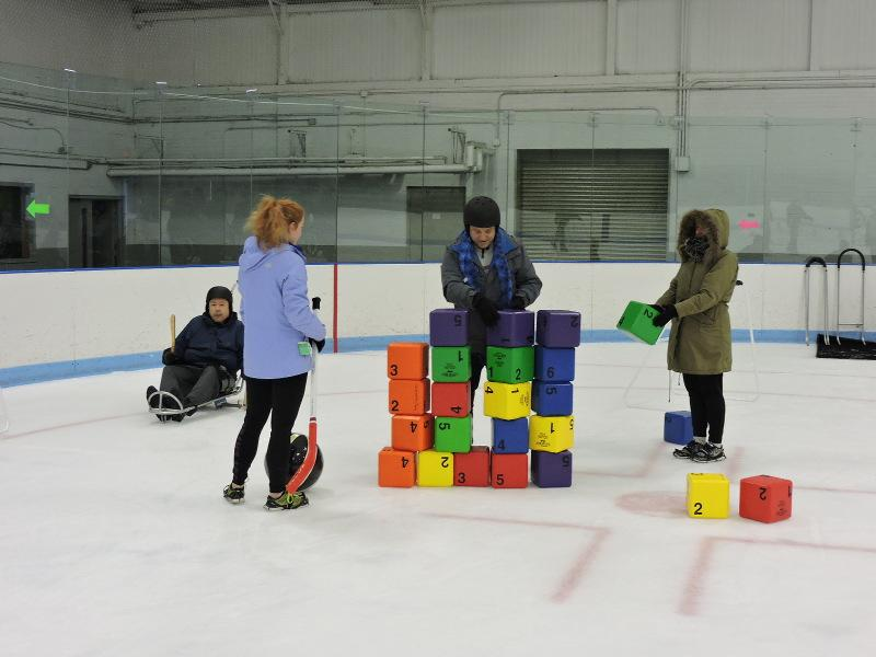 Two people are stacking colorful blocks on the ice. Another person is waiting nearby with a hockey stick and a large ball. Behind them, a man is skating using an ice sled.
