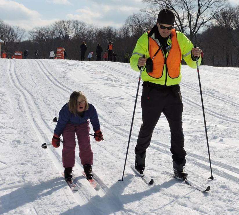 A man and a girl are skiing down a gentle hill next to each other. The girl is leaning forward with her poles stretched out behind her. She is smiling.