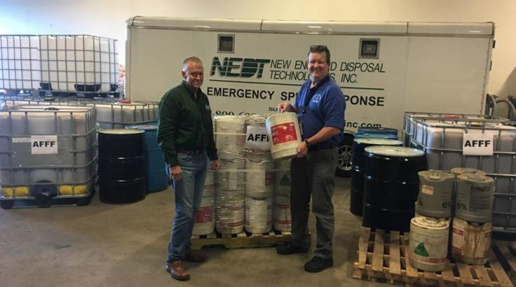 FIREFIGHTING FOAM TAKE-BACK PROGRAM… MassDEP Emergency Response Director Nick Child (right)reviews old containers of legacy firefighting foam with NEDT President Mike Robertson as part of the MassDEP Legacy Firefighting Foam Take-Back Program.