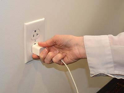 Hand plugging cord into outlet