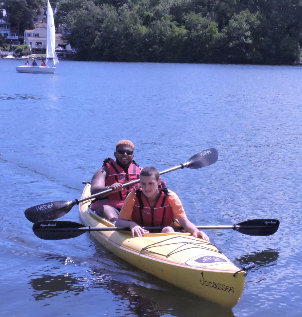 Two kayakers are paddling in a tandem kayak. Behind them, a sailboat is on the water, and houses are visible on the shoreline.