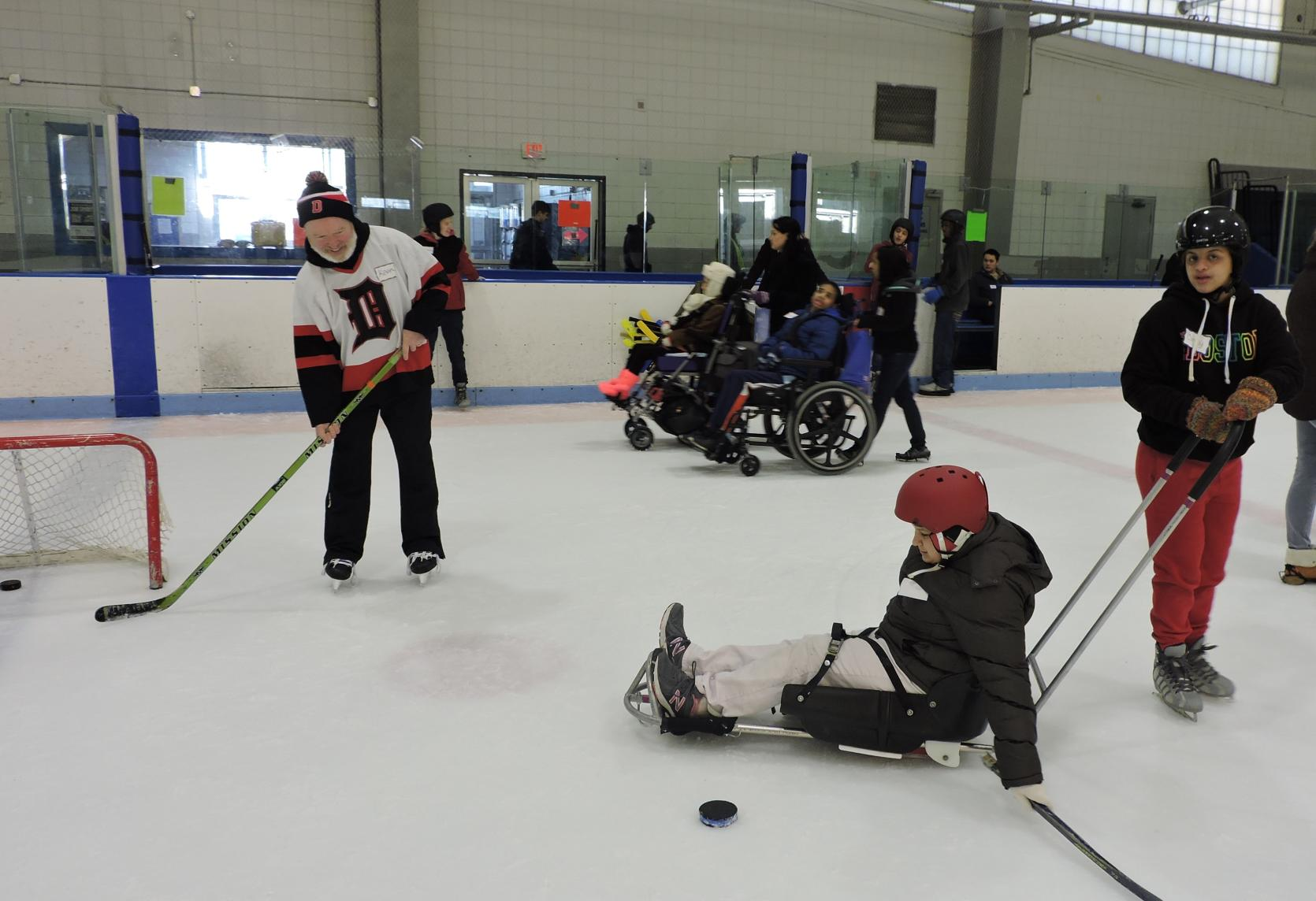 A skater in an ice sled is setting up to shoot a hockey puck at a small hockey net. Another skater is holding onto the handle of the ice sled. The goalie at the net has a stick out to catch the puck. In the background, two skaters in manual wheelchairs are being pushed across the ice.