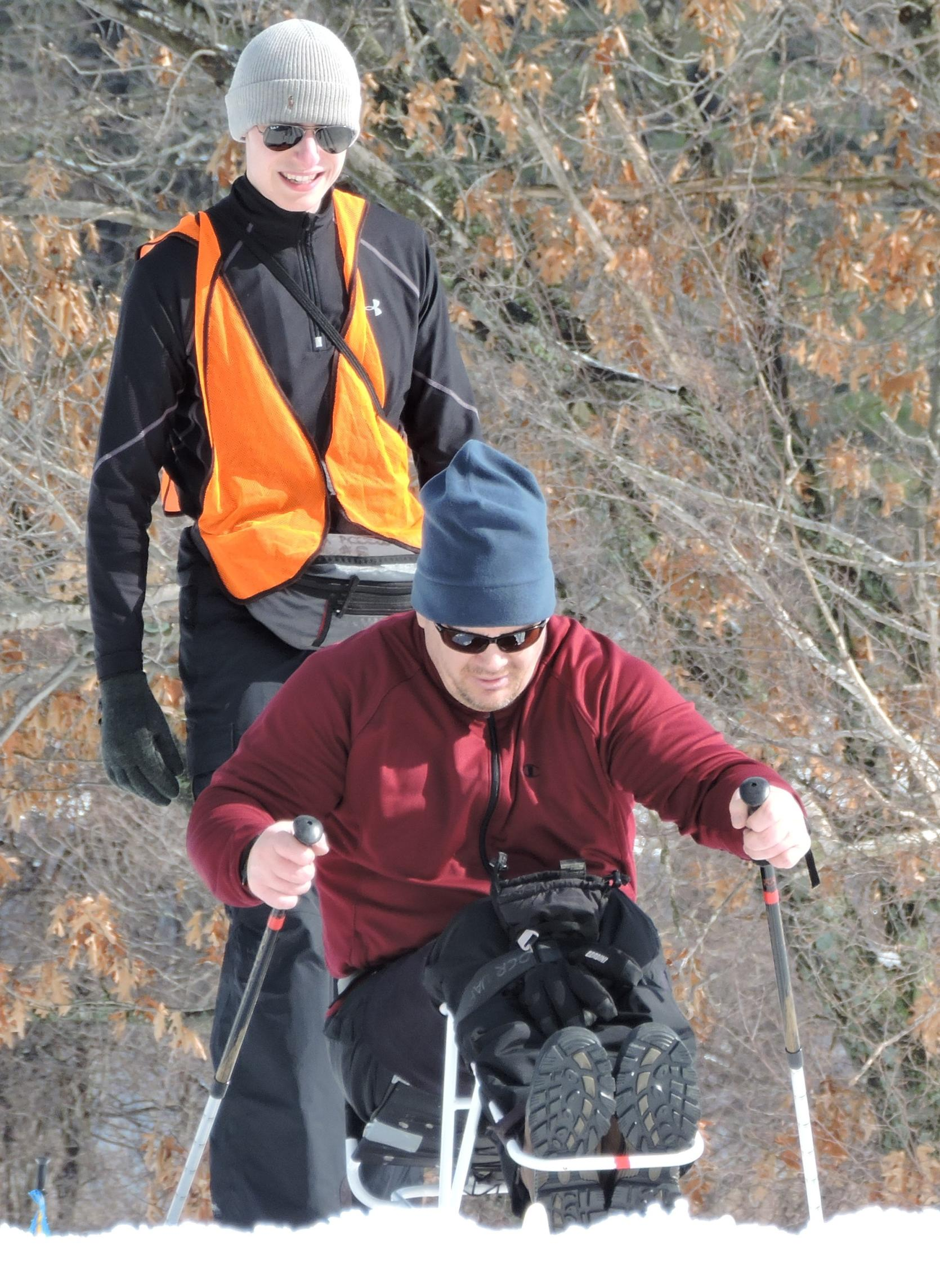 A man in a sit ski is pushing himself up a slight hill using two short ski poles. His knees are bent, and a strap is holding his legs to the sit ski frame. Another person is walking behind him.