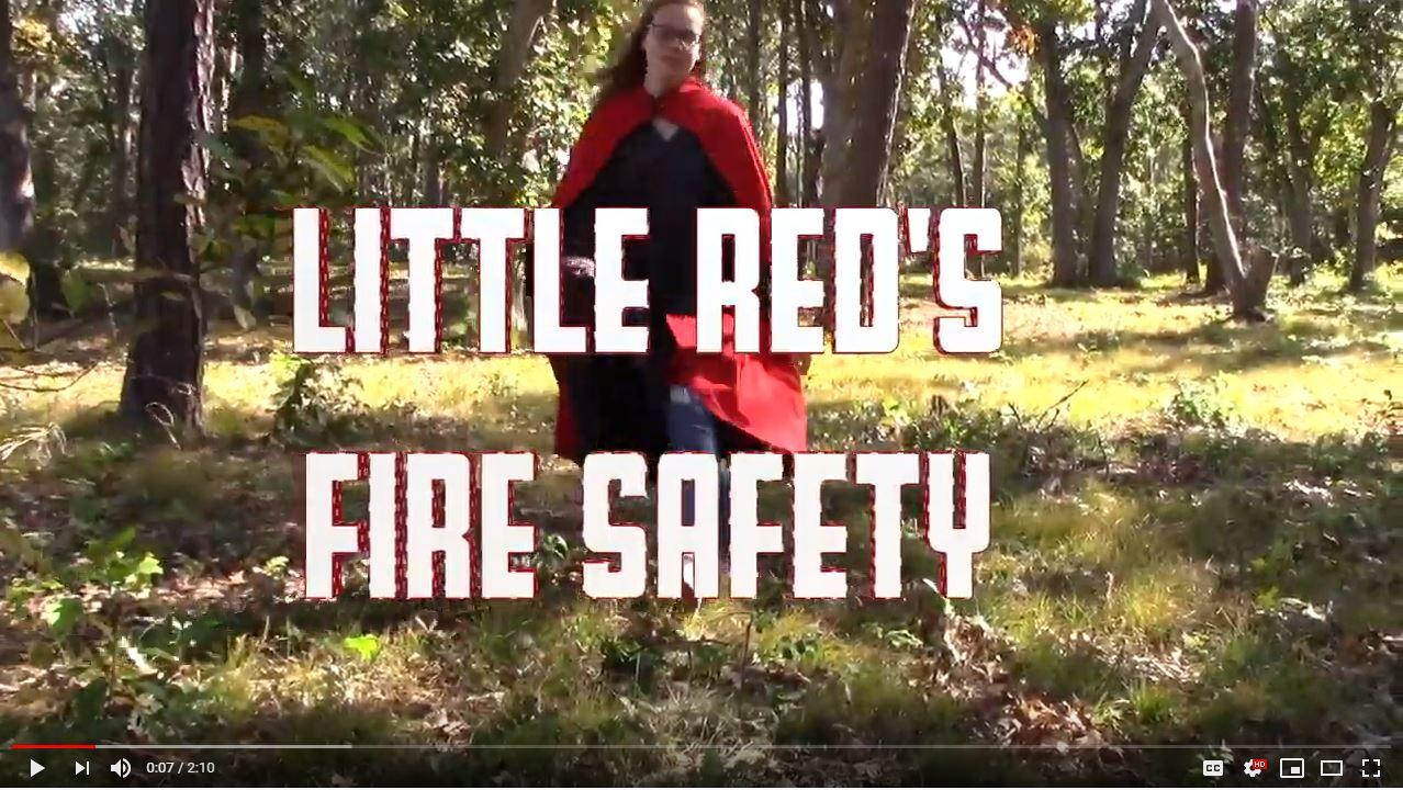 Screen shot from winning video. Girl dressed as little red riding hood skipping through the woods.