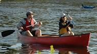 A couple canoeing along the Charles River.