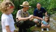 A ranger explaining something to a pair of young children.