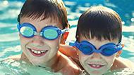 Two boys swimming with googles on