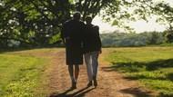 Two people walking along a trail.