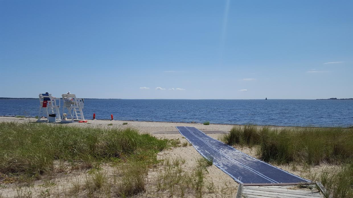 A section of blue beach mat extends from the edge of a boardwalk out towards the water. A second brown section of beach mat runs parallel to the shore line. To the left of the beach mat, two lifeguard chairs sit facing the water. Beach grass is gorinw on either side of the beach mat.