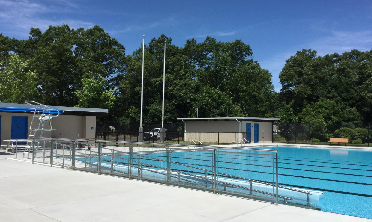 A ramp descends into the water of a pool. near a lifeguard stand. Beyond the ramp, painted lanes are visible on the pool floor.