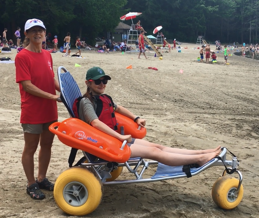 A woman is sitting in a beach wheelchair with a metal frame, fabric seat, and three balloon tires. The chair has large orange floats under the armrests. The woman's legs are extended out in front of her and resting o n the chair. She is wearing a life vest. Another woman is standing behind her and holding onto the back of the chair.