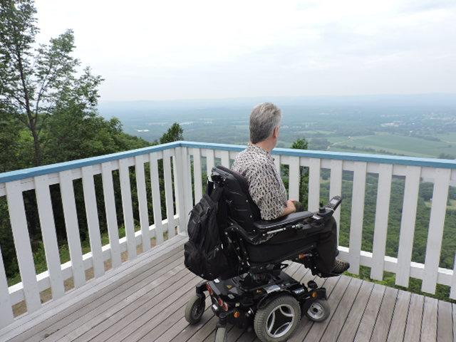 A man in a power wheelchair is sitting at the railing on a deck. The Connecticut River is visible in the distance beyond the railing.