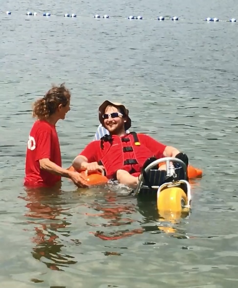 A man is floating in the water in a floating beach wheelchair. He is wearing a life jacket and resting against the fabric backrest of the chair. A woman is standing beside him, with her hands on the frame of the chair.