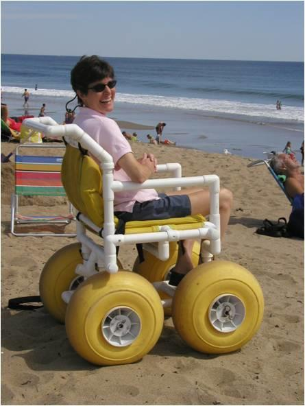 A woman is sitting in a beach wheelchair made of PVC tubing, in front of the ocean. The chair has large yellow balloon tires. The woman is smiling at the camera.