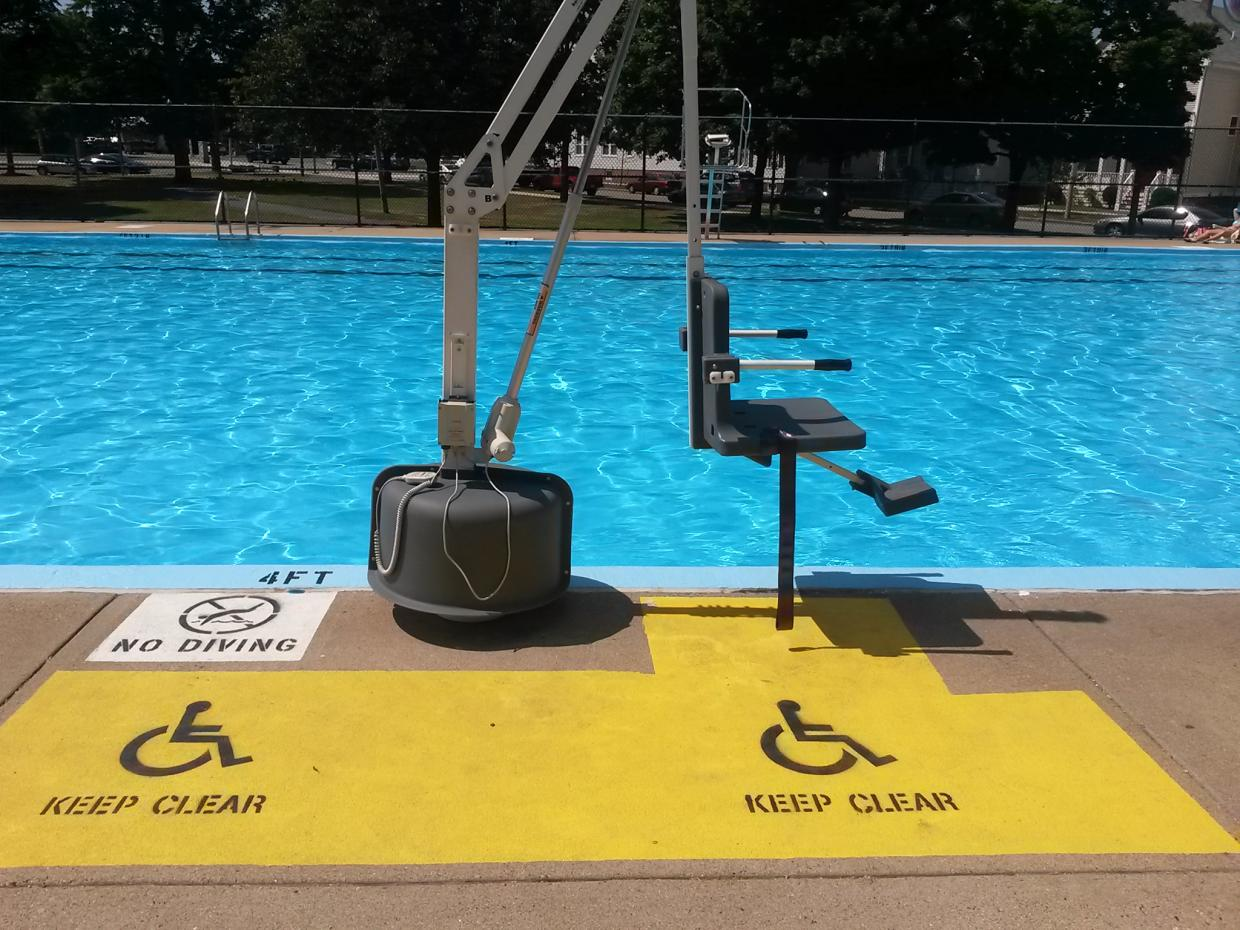 A chair lift is located next to a pool. The chair has arms and a foot rest, and is attached to the end of a telescoping arm that rises up into the air. The concrete walkway near the lift is painted yellow. A figure in a wheelchair and the words KEEP CLEAR are also painted on the walkway.