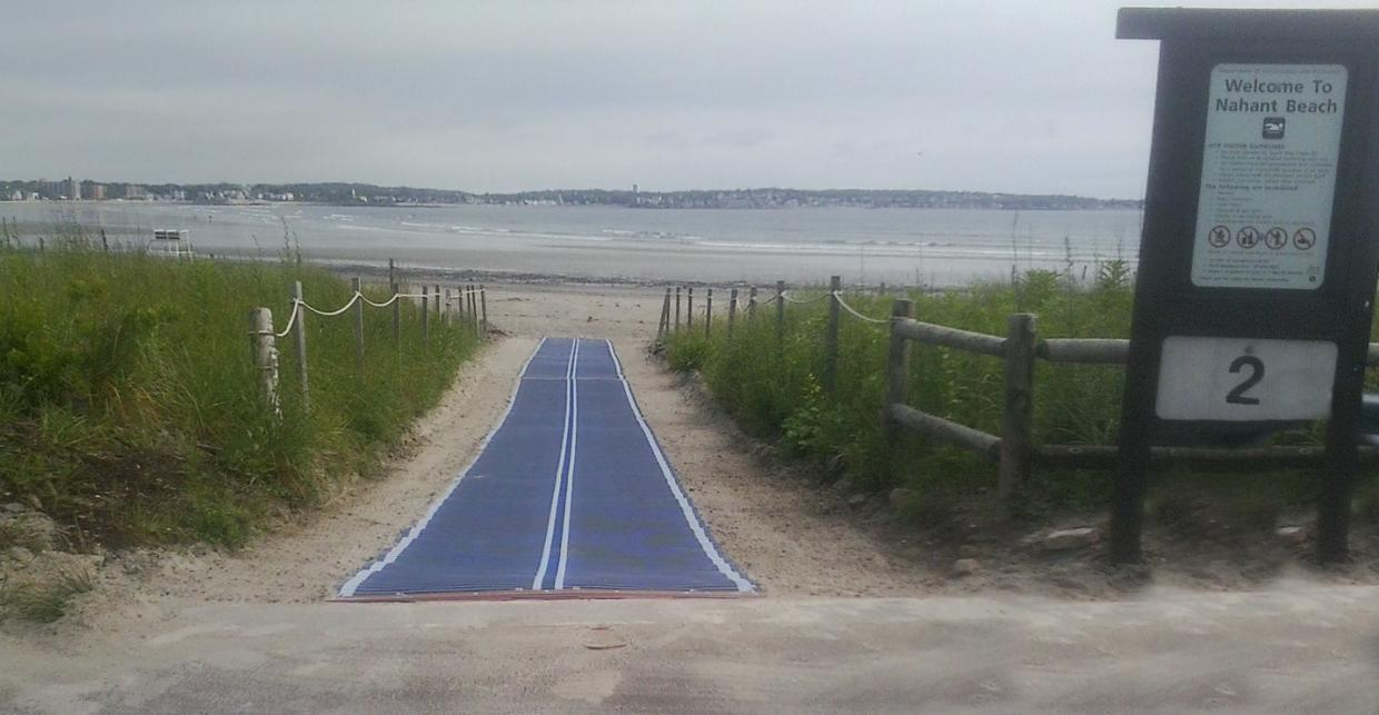 A section of blue beach mat runs from the edge of a paved area down a sloped sandy path towards the water. Sandy dunes are on either side of the beach mat, roped off. A sign reads Welcome to Nahant Beach. The sign has a large number 2 below it.