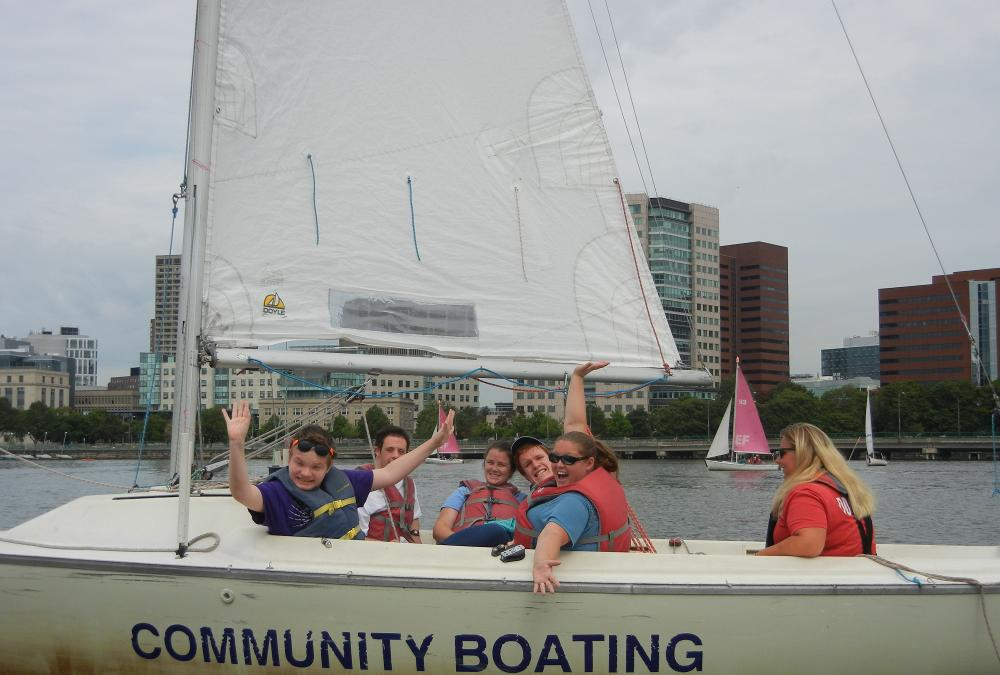 A dozen people are sharing a sailboat. The people in the front of the boat are smiling and waving, while one person in the back controls the rudder.