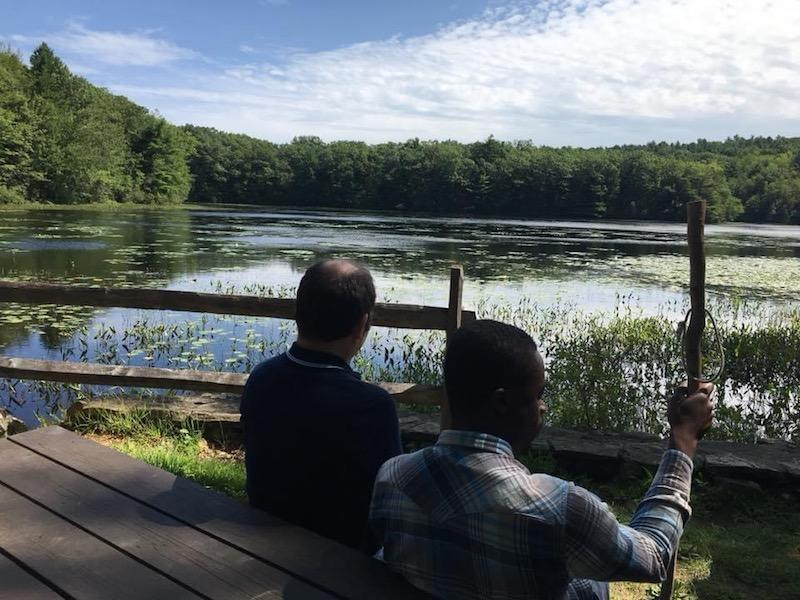 Two men sit at a picnic table looking out over a lake. One of the men is holding a walking stick.