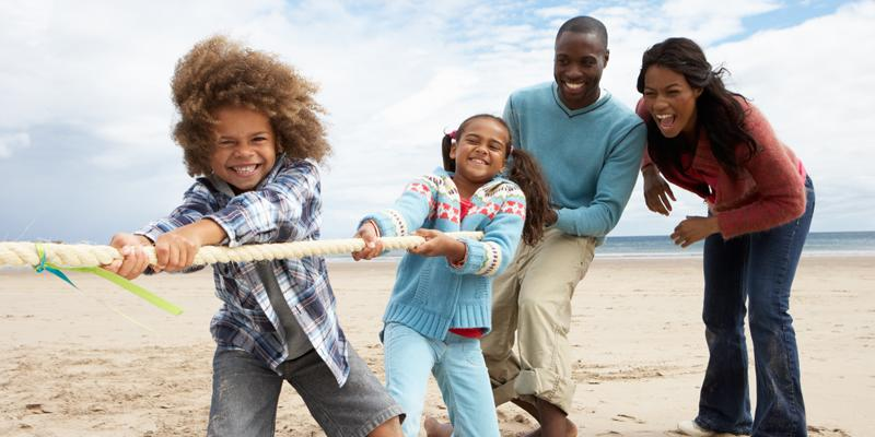 Black family playing tug of war on beach
