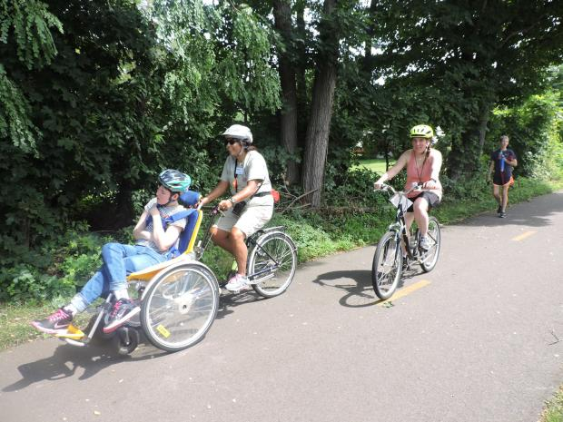 A photo of three cyclists riding together on a bike bath. The two cyclists in front are riding a tandem cycle together. The woman in the front of the tandem cycle is sitting in a seat with a back and head support. The woman behind her is pedaling and steering the cycle. The other cyclist is following on an upright bicycle.