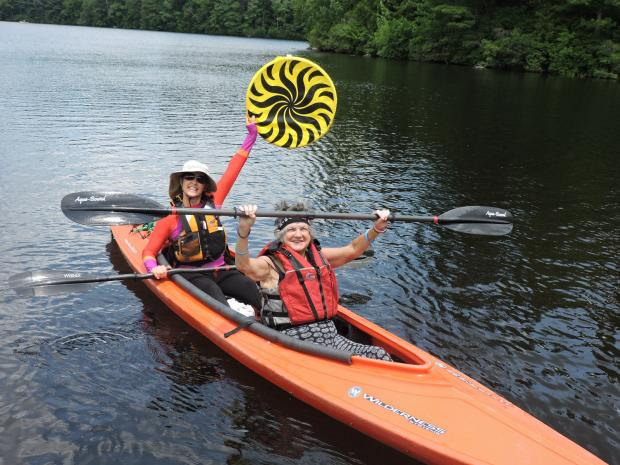 A photo of two women sitting in a tandem kayak on the water. The kayak has a large, open cockpit. The woman in front is holding up her paddle with both hands and smiling. The women behind her is holding up a large disc and also smiling.