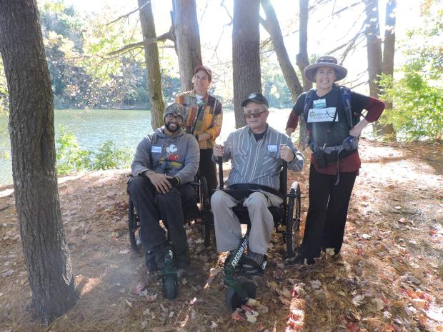 A photo of four smiling hikers in the woods next to a pond. Two of the hikers are using hiking wheelchairs, and two hikers are standing. The hiking wheelchairs have levers that the hikers push forward to move themselves.