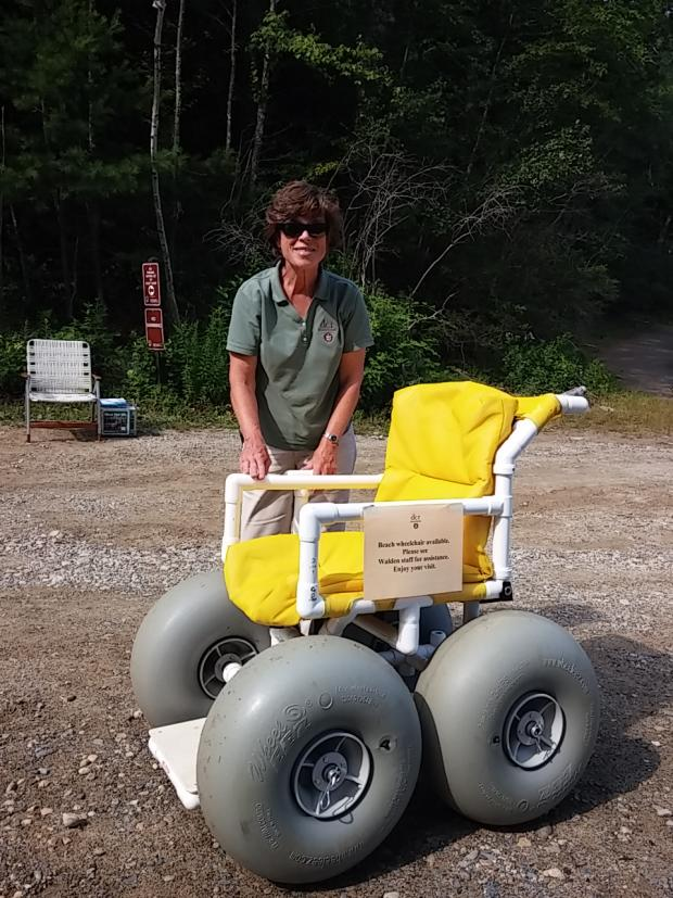 A photo of a woman in a DCR uniform standing behind a beach wheelchair and smiling. The beach wheelchair has large grey balloon tires and yellow cushions. The chair is made out of PVC pipe.