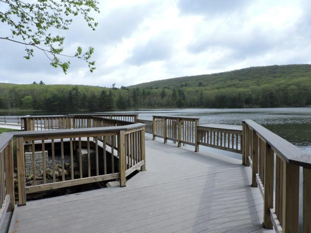A photo of wooden pier with railings that hangs over the water of a pond. Two sections of the railing are lower and have broad tops to rest against. A path running along the shoreline connects to the pier at the far end. Wooded hills are visible on the far side of the lake.