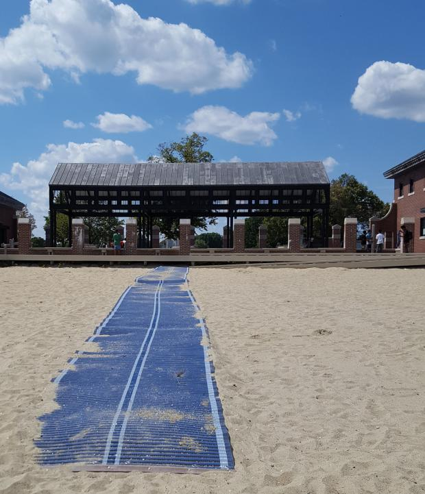 Blue beach mat laid across the sand runs up to the bottom of a wooden ramp. A pavilion and a brick building are visible in the background.