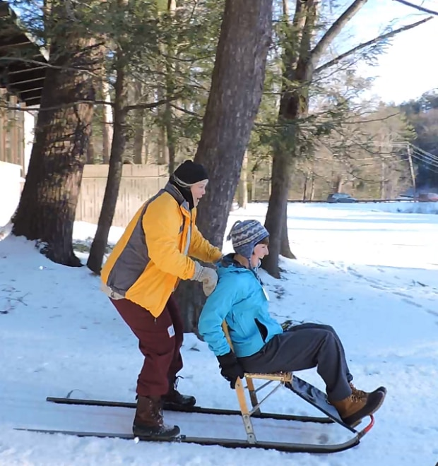 Two women are using a kicksled. The woman on the back is standing on the runners, while the woman in front sits in the chair. They are sledding down a hill and laughing.