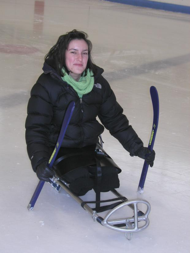 A young woman is sitting in an ice sled, holding two short hockey sticks with picks on the end. The sled is strapped across her legs. Her legs end at the knee.