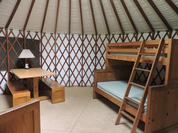 A view inside a  round room with a wooden floor and wooden lattice over canvas walls. The roof is also canvas, stretched over beams. The room has a table with two benches, and a bunk bed with a double mattress on the bottom and a single mattress on the top. A ladder leads to the top mattress.