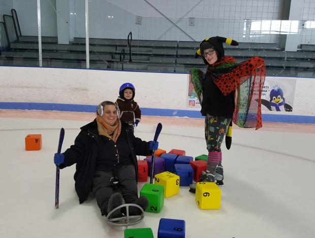 A woman in an ice sled, a girl on skates, and a young boy are standing in a pile of colorful blocks. They are smiling at the camera. The girl is spreading a colorful spotted cape with her arms, and wearing a hat with ears and a plush tail.