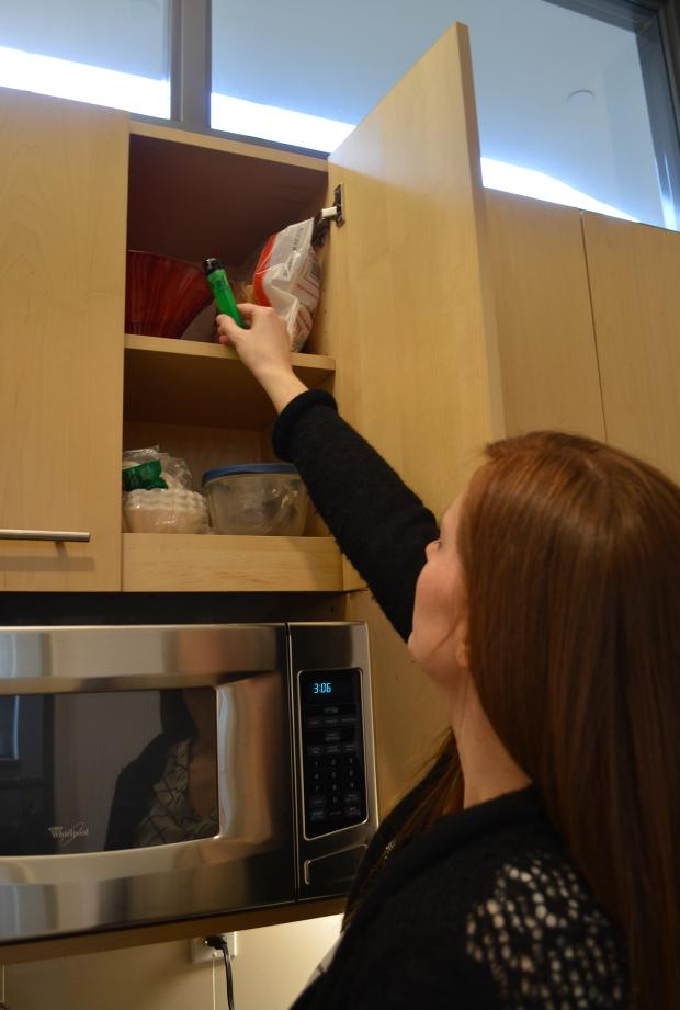 Adult placing matches in high cabinet out of reach of children