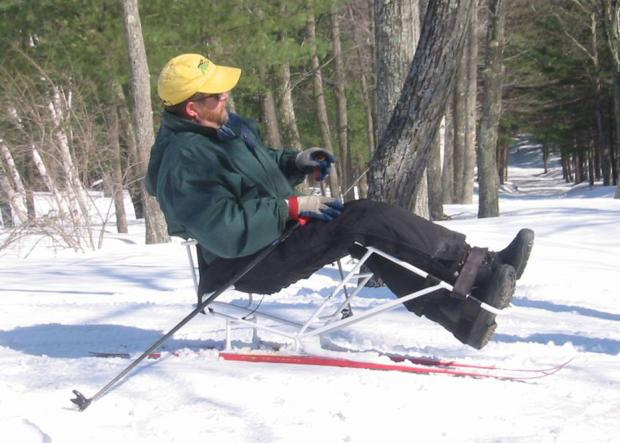 A skier is sitting in a sit ski with frame that bends up at the knees. The skier's kegs are strapped into the ski frame. The skier is using two short ski poles to push himself through the snow.