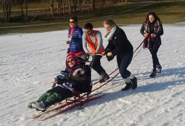 A sit-skier is using a straight-legged ski with handles and outriggers. Two people standing behind the sit ski are pushing on the handle to move the ski up a slight hill. Another person is holding a long rope attached to the back of ski. A fourth person is jogging alongside.