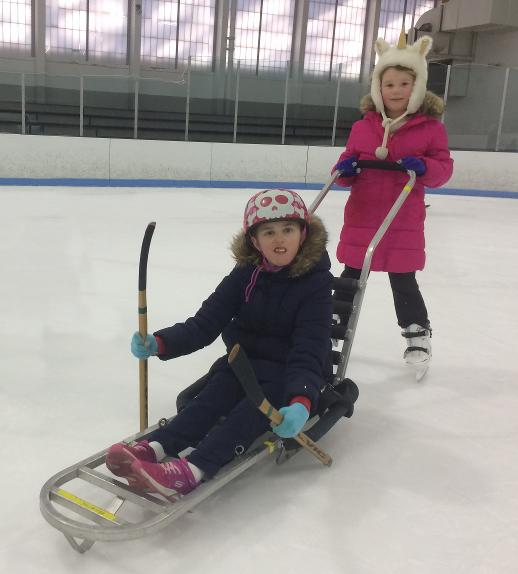 A young child wearing a helmet is sitting in a small ice sled, holding short hockey sticks with ice pics on the ends. Another child wearing skates is standing behind the sled, pushing the curved handle on the back.
