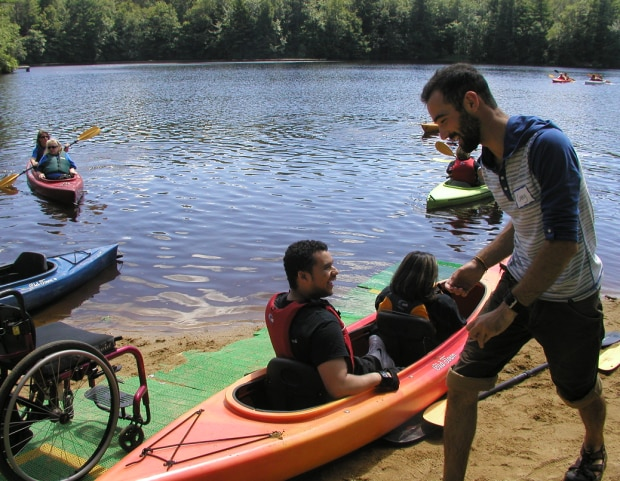 A tandem kayak sits on the beach, next to a run of beach mat. A wheelchair is sitting on the bach mat. Two people are sitting in the tandem kayak, facing the water. A man is walking towards the back of the kayak. Several other kayakers are paddling in the water.