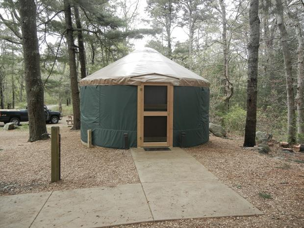 The round walls of this yurt are covered in green canvas. The roof is beige vinyl that slopes up to a domed skylight. A ground level, L-shaped cement walkway transitions smoothly from the parking area to the interior of the yurt.