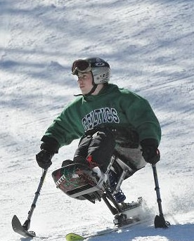 A skier skis down a hill on a mono ski. The skier has two short poles with ski blades on the end of them, which the skier is pressing against the snow to steer.
