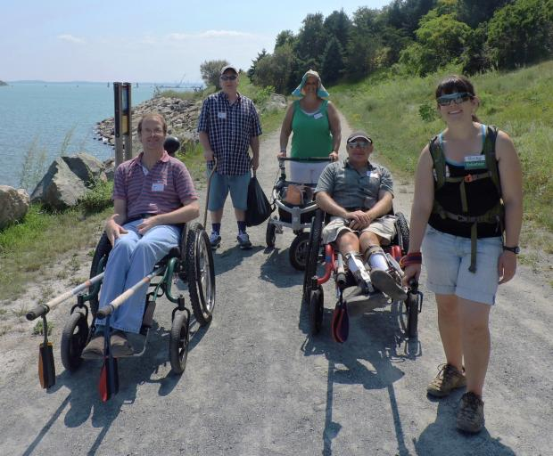 Five hikers are standing on a smooth dirt path. The ocean is on one side of them and a grassy, sloping hillis on the other. Two of the hikers are sitting in wheelchairs with rugged tires and rickshaw poles attached to the front. One hiker is using a cane, and another is using an all-terrain walker with three wheels. One of the hikers in a wheelchair is being pulled by a young woman with a volunteer name tag.
