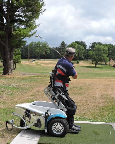 A man is using a ParaGolfer at the driving range. The ParaGolfer has a triangular base with two wheels in the front and one in the back. The seat is mounted on a hinged frame that can be raised. The man using the Paragolfer is strapped into ths seat with a harness, and is raised up to a standing position. His golf club is swung over his shoulder. he is looking down the driving range.