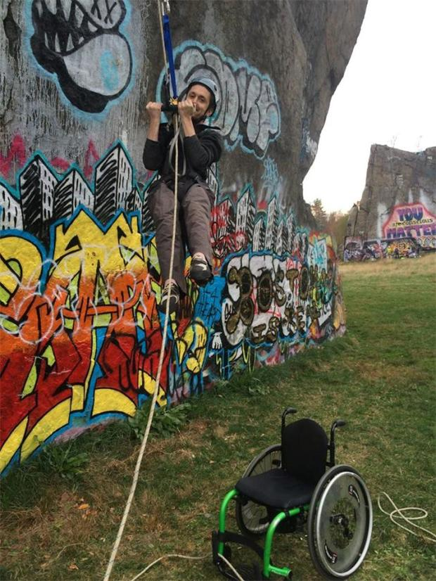 A person wearing a harness and a helmet is holding into a rope, hanging about 6 feet off of the ground. Behind them is a   rock wall covered in colorful graffiti. Below them, a bright green wheelchair is sitting on the grass.