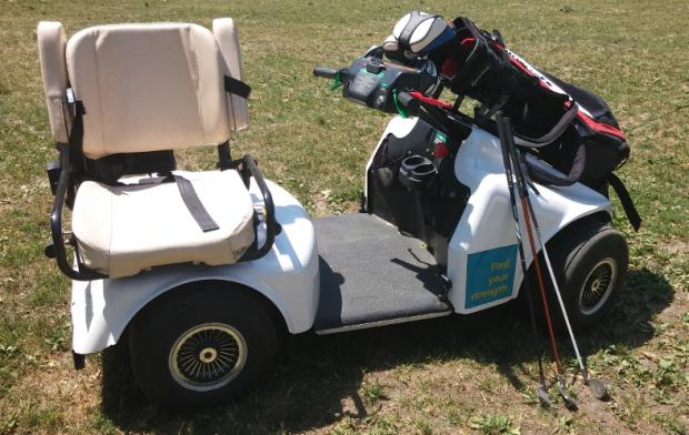 A SoloRider golf cart is sitting on the grass, with a bag of golf clubs resting in a rack on the hood. The cart has four wheels, and a flat smooth area between the front of the cart and the rear. The cart has two hand controls mounted on a column that extends from the hood. The seat is padded, with arm rests that swing up. The seat is turned so that it is facing 90 degrees away from the front of the cart.