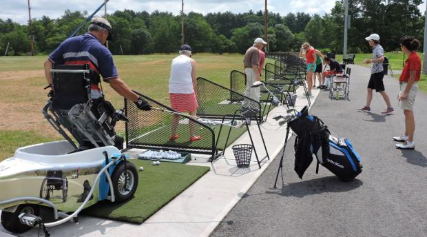 A group of people is standing on the driving range, driving golf balls. Several other people are standing behind them, watching and offering advice. one of the golfers is using a ParaGolfer to hold him upright while he swings. The reflection of a wheelchair, a service dog, and another ParaGolfe user are visible in the side of the ParaGolfer.
